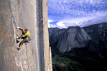 Tommy Caldwell on the head wall of the Dihedral Wall during his first ascent of the route on El Capitan in Yosemite National Park in the Sierra Nevada Mountains, California. He is crack climbing a 5.13 pitch. Half Dome is visible in the distance.