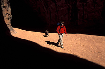 Todd Snyder and his canine companion walk through a swath of light somewhere around Lake Powell in Utah.