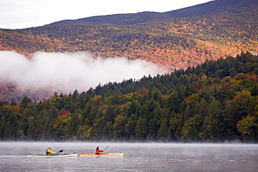 Fit, middle-age couple sea-kayak on Lake Placid in autumn, New York, USA.