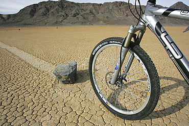 "DEATH VALLEY, CA, JANUARY 07: A mountain biker staring at a ""sliding rock"" on The Racetrack, a dried lake bed in Death Valley National Park, California on January 07, 2006."