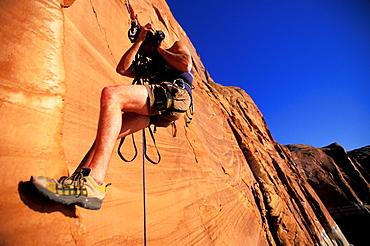 Craig Luebben negotiates his camera while climbing in Lake Powell, Utah.