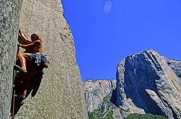 Rock climber Mike Lewis jams up the third pitch of a thin finger crack in Yosemite National Park. El Capitan is in the background.