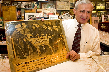 """Sam Sianis poses in Chicago's landmark Billy Goat Tavern with a newspaper photograph of his uncle Sam Sianis and the famous goat that put the """"Curse of the Billy Goat"""" on the Chicago Cubs baseball team."""