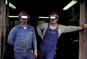 Two welders pose in the frame of a door.