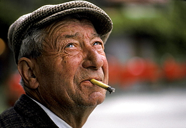 An older man holds a cigarette between with teeth and smiles.