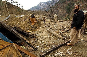 Men from the village of Gangwal, which was devastated in the 2005 earthquake, show makeshift shelters that villagers constructed themselves after the quake, in the upper Allai Valley, NWFP, Pakistan.  Most of the villagers fled to tent camps at lower elevations to spend the winter, leaving just a handful of families to look after livestock and possessions. The people of this remote area are  Pashtun and until the earthquake, neither the government nor the military had much presence or influence in the region.