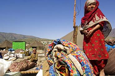 A girl in the Meira tent camp for earthquake survivors stands on top of a pile of her family's belongings as they wait for transportation from the camp, where they have spent the winter, back to their devastated mountain village, in the NWFP, Pakistan.  The Pakistani army, which runs the camp, has mandated that the camps be cleared by early April, despite the fact that many families are afraid or unprepared to return to their devastated homes. The Meira Tent camp (also called Mera, or Maria camp), is located on the Indus River in the Battagram district.  The camp, the largest for displaced people in Pakistan, hosts over 21,000 earthquake survivors, primarily from the Allai valley in Pakistan's NWFP, one of the areas worst-hit by the October 8, 2005 earthquake.