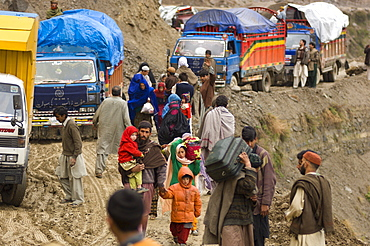 On the the road to the Allai Valley, a Pashtun family carries luggage past trucks that are stuck in mud and landslide debris-the trucks are full of  other  families and their possessions traveling back to their mountan villages, Battagram District, Pakistan's Northwest Frontier Province.  The region was one of the worst-hit by the October 2005 earthquake, and aftershocks and  heavy rains continue to trigger landslides, which have hampered reconstruction efforts and the return of earthquake survivors  to their mountain villages from the low altitude tent camps where many spent the winter.