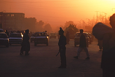 Setting sun highlights traffic and traffic cops in the center of Mazar-i-Sharif, Balkh Province, September 22, 2002. Mazar-i-Sharif  (also spelled Mazar-e Sharif) is the largest city in Northern Afghanistan, and is capital of the Balkh province.  It is an important city for Afghanistan's Shiite Muslims, who come to worship at the famous Blue Mosque.