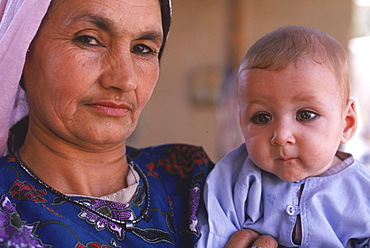 A Tajik woman holds a baby with kohl rimmed eyes, in the compound of an extended, traditional family in Mazar-i-Sharif, Balkh Province, September 25, 2002.  The Tajik are one of the larger ethnic groups in Afghanistan, second only to the Pashtun people.