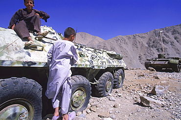 Children play on a tank in the Panjshir Valley while waiting for ceremonies to begin in honor the one year anniversary of the assasination of Ahmad Shah Masood, September 9, 2002. The Panjshir Valley was a stronghold for the Tajik people and the famous commander Masood in their struggle first against the Soviets and then against the Taliban.  The valley and villages of the Panjshir were subjected to heavy bombing and destruction during the Afghan-Soviet war, but was never fully occupied.  Now it is the heartland for the powerful Tajik ethnic group, the second largest in Afghanistan, who came to partial power after the fall of the Taliban.