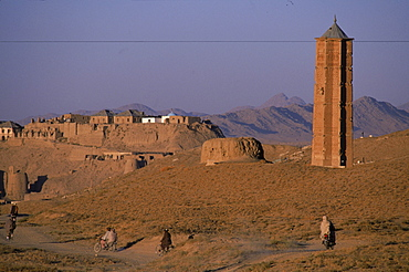 Men on bikes ride past an ancient  brick minaret  toward the old walls and citadel of the town of Ghazni, Afghanistan, October 1, 2002. Made of brick decorated with Kufic and Naksh Script and floral motifs, the  minaret dates back to  the early 12th century and was built by Sultan Masud III of the Ghaznavid Dynasty, who ruled over an empire encompassing much of Afghanistan, Northern India, Persia and Central Asia. The minaret was once three times as tall as its current 70 feet, and is thought to have been part of a large mosque complex. Now an  important truck stop on the road to Kandahar, Ghazni, located on the Lora River at the elevation of 2,225 meters, is the capital of Ghazni province with a population of 35,900, and is a  market for sheep, wool, camel hair cloth, corn, and fruit.