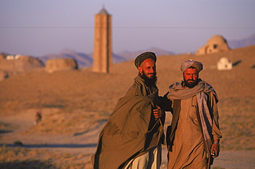 Afghan men pause on the road with an ancient  brick minaret  and many shrines in the background, outside of Ghazni, Afghanistan, October 1, 2002. Made of brick decorated with Kufic and Naksh Script and floral motifs, the  minaret dates back to  the early 12th century and was built by Sultan Masud III of the Ghaznavid Dynasty, who ruled over an empire encompassing much of Afghanistan, Northern India, Persia and Central Asia. The minaret was once three times as tall as its current 70 feet, and is thought to have been part of a large mosque complex. Now an  important truck stop on the road to Kandahar, Ghazni, located on the Lora River at the elevation of 2,225 meters, is the capital of Ghazni province with a population of 35,900, and is a  market for sheep, wool, camel hair cloth, corn, and fruit, and continues to be a haven for  Taliban insurgents.