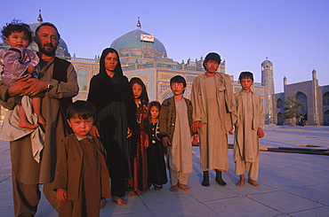 A large Turkomen family who have made a pilgrimage to the shrine of Hazrat Ali at the Blue Mosque in Mazar-i-Sharif, pose for a photo in front of the temple complex.  The Blue Mosque is considered to be one of the most important and beautiful buildings in Afghanistan