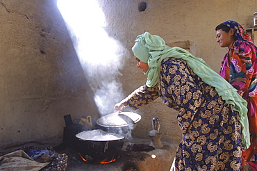 Young Tajik women cook on clay stove in the compound of an extended family in Mazar-i-Sharif, Balkh Province.  The kitchen is open air, with wood fires stocking clay ovens and stoves, which allow several huge pots to be simmering at once.