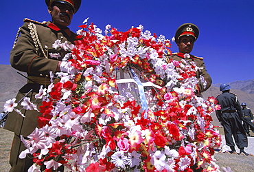 Elaborate flower wreaths are brought by Afghan soldiers as tokens of respect to  the shrine of Ahmad Shah Masood, on the one year anniversary of Masoods assasination, at a ceremony in the Panjshir Valley, Afghanistan, September 9, 2002. Masood was a revered mujahedin leader who fought the Soviets in the Afghan-Soviet war, and who also was one of the main leaders of the Northern Alliance which opposed the Taliban and helped the US Military in their defeat.  Masood was assasinated by what are thought to be Al Queda operatives on Sept. 9, 2001.  A shrine has been erected in the Panjshir  Valley, near the village of Bazarak, from where he led much of his resistance to both the Soviet and Taliban forces, to honor this latest of Afghan war heros.