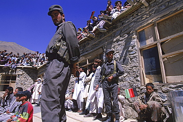 Armed guards keep an eye on the crowds during a ceremony below the shrine of Ahmad Shah Masood in the Panjshir Valley, September 9, 2002. Masood was a revered mujahedin leader who fought the Soviets in the Afghan-Soviet war, and who also was one of the main leaders of the Northern Alliance which opposed the Taliban and helped the US Military in their defeat.  Masood was assasinated by what are thought to be Al Queda operatives on Sept. 9, 2001.  A shrine has been erected in the Panjshir  Valley, near the village of Bazarak, from where he led much of his resistance to both the Soviet and Taliban forces, to honor this latest of Afghan war heros.