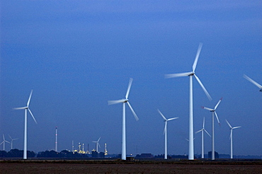 A wind power installation towers over the Shell-DEA oil refinery plant near the town of Heide in the German state of Schleswig-Holstein.  Situated between Germany's two coastlines, the northern state has invested heavily in new, renewable energies.  In 2005, there were 2.595 wind turbines in Schleswig-Holstein, generating over 30% of the state's energy.  Wind power accounts for 6,7% of Germany's overall energy needs.