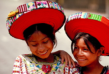 Two Mayan girls laughing in traditional clothes.