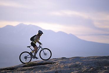 Retired professional mountain biker Sara Ballantyne mountain biking on the slickrock in Moab, Utah at sunset.