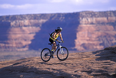 Sara Ballantyne, a retired professional mountain biker, mountain bikes on slickrock along a sandstone cliff in Moab, Utah.
