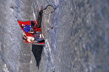 Beth Rodden and Tommy Callwell hang out on a rock ledge so Tommy can rest from rock climbing Dihedral wall, a multi pitch route on El Capitan in Yosemite National Park, California.