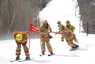 A group of fireman are in the annual fireman hose race at Sunday River ski resort in Bethel, Maine.