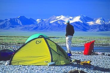 A camper on the coastal plain, 1002 Area, of the Arctic National Wildlife Refuge looks back towards the mountains, Alaska.