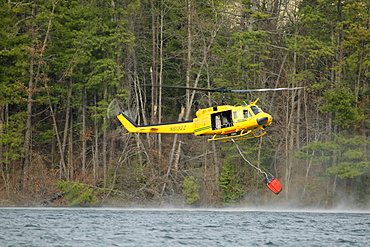 NC Forestry Service helicopter dips its bucket into Lake Julian while fighting a fire near Arden, NC.