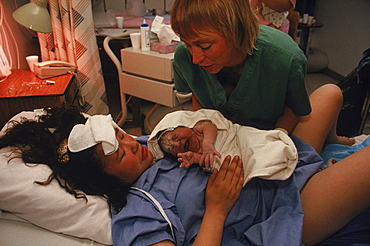 Mina Liasa, 24, flew 190 miles to deliver her second child. Here she sees the baby for the first time. Leanne Tyler, an outpost nursing student helps. Baby boy is named Jerry.