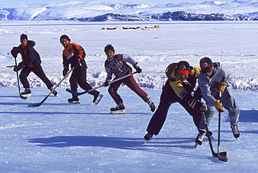 Kids playing hockey on ice in front of the town. An indoor rink is being built so they can play in the summer and during long cold winter months.