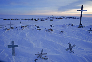 The cold sunlight of early March brushes grave markers above Igloolik, one of Nunavut's 28 isolated towns. Winter night lasts seven weeks, and July heat averages just 43° F.