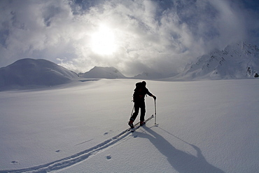 Backcountry skier crosses glacier under late day stormy sky.
