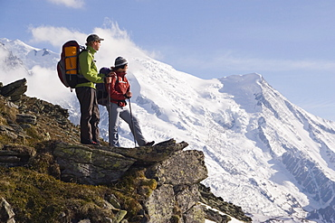 Two hikers stand on an overlook near Mont Blance in France.