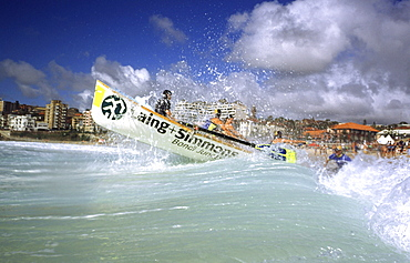 A group of people on a surf boat during a surf carnival in Sydney, Australia.