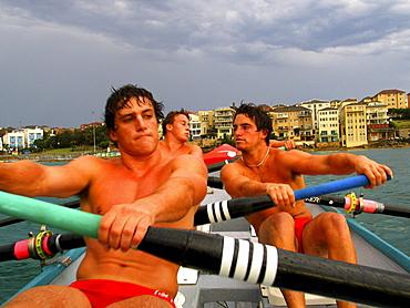 Three men onboard a surf boat in Sydney, Australia.