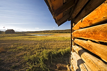 The side of log barn with ranch house in the backround on the Uncompahgre plateau, Colorado.