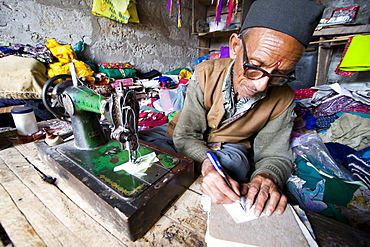 Man sewing goods in small village, India