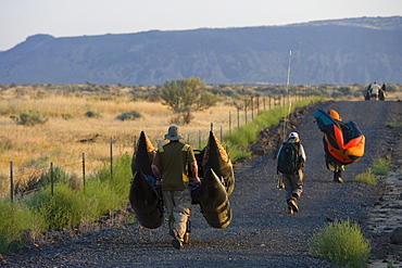 Flyfishermen with their gear walk to a hidden desert lake in eastern Washington.