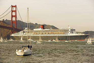 A cruise ship sails under the Golden Gate Bridge in San Francisco, California.