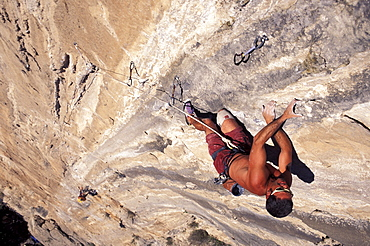 A man climbing a big wall with another man below him in El Potrero Chico, Mexico (High Angle Perspective).