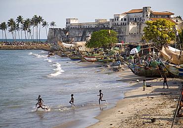 Children running into the sea in Elmina