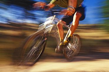 A Mt. biker speeds by on a mountain trail.