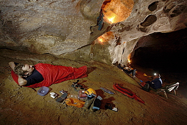 A cave explorer relaxing in his sleeping bag before having to get up and put on his cold wet clothes from the day before.