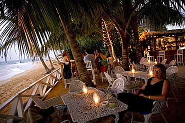 A woman has a drink at a beach bar in the Dominican Republic