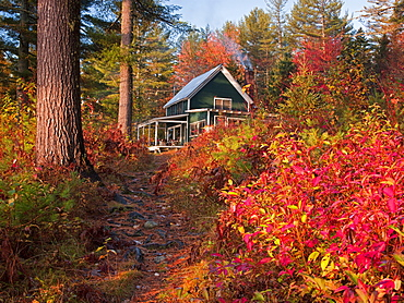 Colorful fall foliage defines the pathway from Richardson Lake to this historic hunting and fishing camp in western Maine.  Ben Pearson,  the fourth generation in his family to own the camp,  is carefully restoring the main building,  three boat houses an