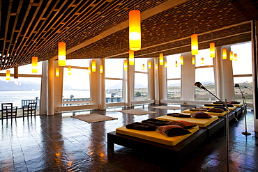 PUERTO NATALES, PATAGONIA, CHILE. The inside of a fancy hotel where beds are laid out and the warm glow of lights invite relaxation and solitude.
