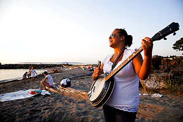 A woman plays the banjo at sunset at a state park beach.