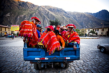 OLLANTAYTAMBO, SACRED VALLEY, PERU. A group of men dressed in traditional clothing in the back of a pickup truck in a  small town.