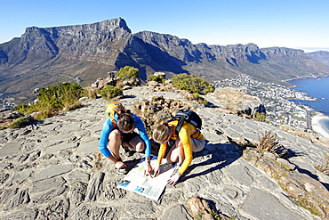 On top of Lion's Head with Table Mountain in the back Katrin Schneider and Susann Scheller are looking at a map of the city of Cape Town. South Africa.